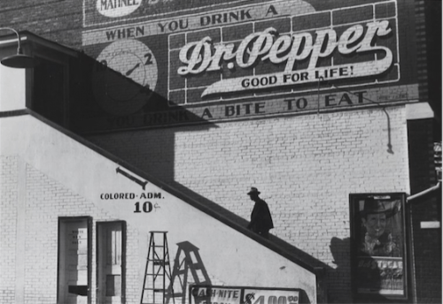 """Marion Post-Wolcott, """"Negro Man Climbing the Stairs to a Movie Theatre, Belzoni, Mississippi,"""" 1939, 18 x 19.5 inches, collection of John Goodwin and Michael-Jay Robinson."""