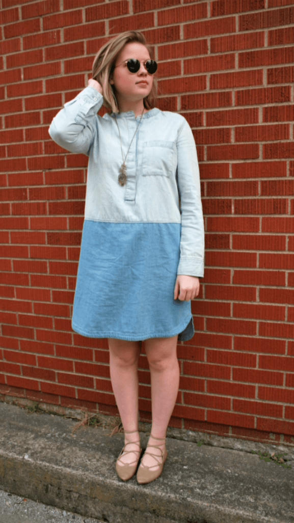 Modeling a denim dress with gold accessories and lace up flats.