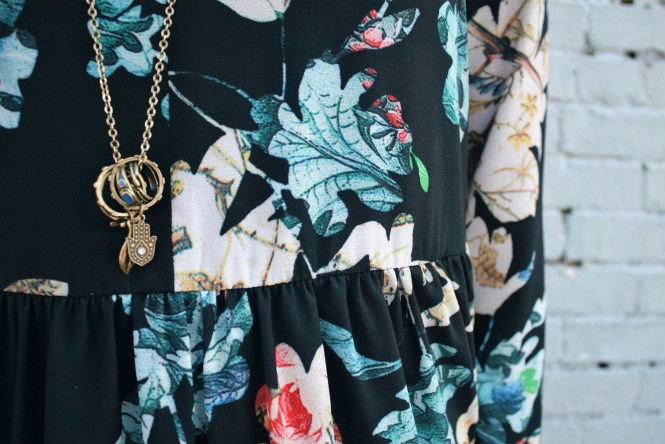 Close up image of gold necklace and floral print.