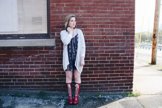 Modeling a printed romper, silver cardigan, and lace-up Roma boots.
