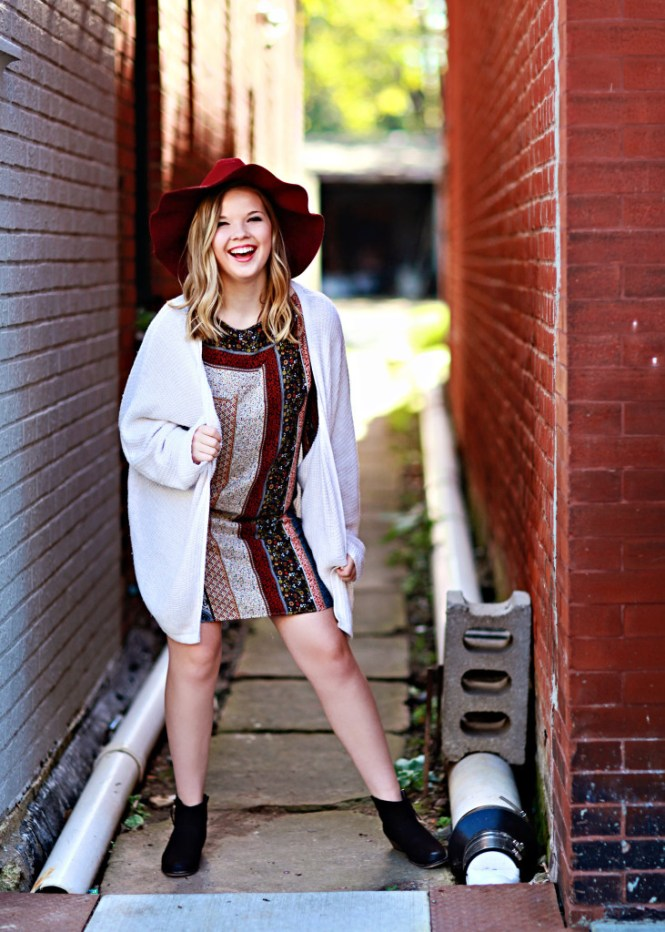 Senior Picture: Style Guide. Modeling a printed dress and oversized cardigan with a floppy hat and brown booties. Posing in a brick alley.