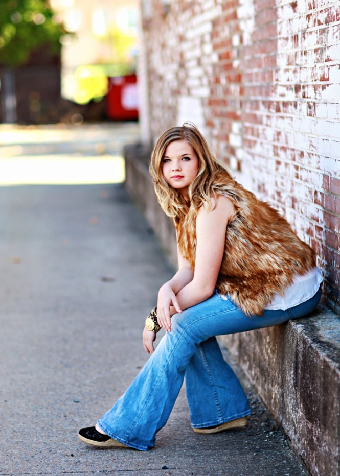 Senior Pictures: Style Guide. Modeling a fur vest and flare jeans. Posing against a brick wall.