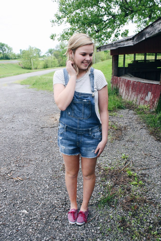 The Overall Scoop. Modeling a pair of short overalls, a grey and white striped tee, and maroon polka dot Keds.