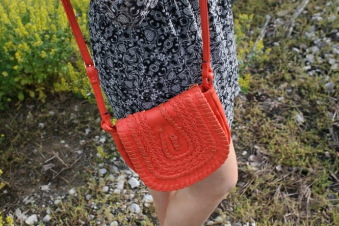 A Printed Romper, Internship, and Fork Necklace. Close up of the orange purse.