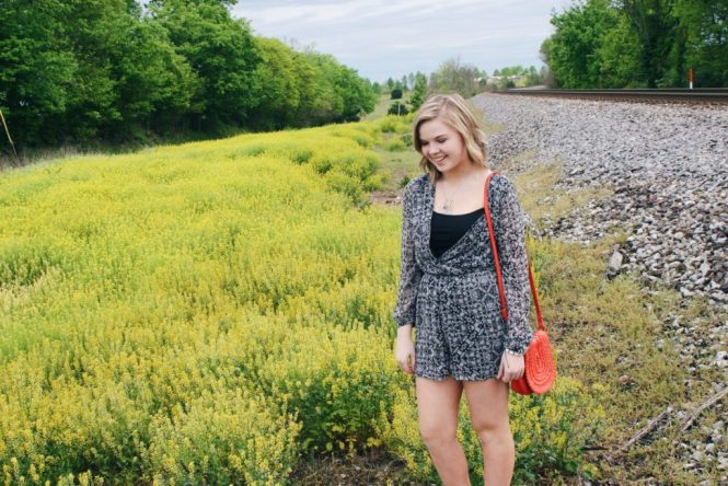 A Printed Romper, Internship, and Fork Necklace. Modeling a printed romper, silver statement necklace, and a vibrant orange purse.