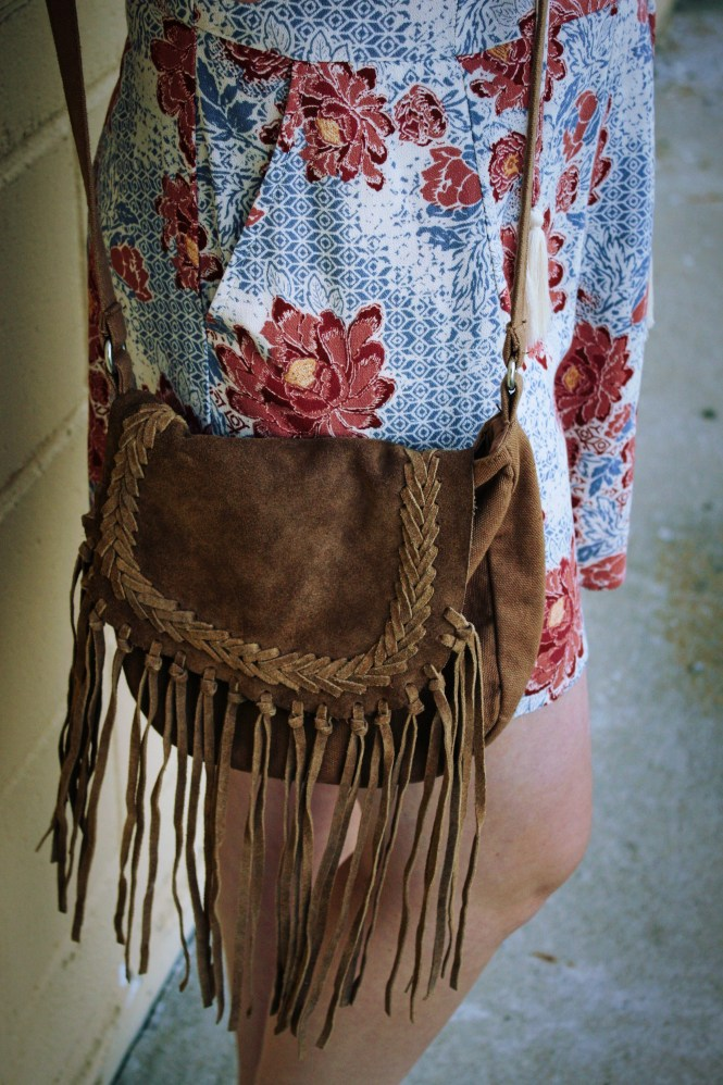 K+K Romper. Modeling a romper, denim jacket, fringe crossbody, and platform sandals.
