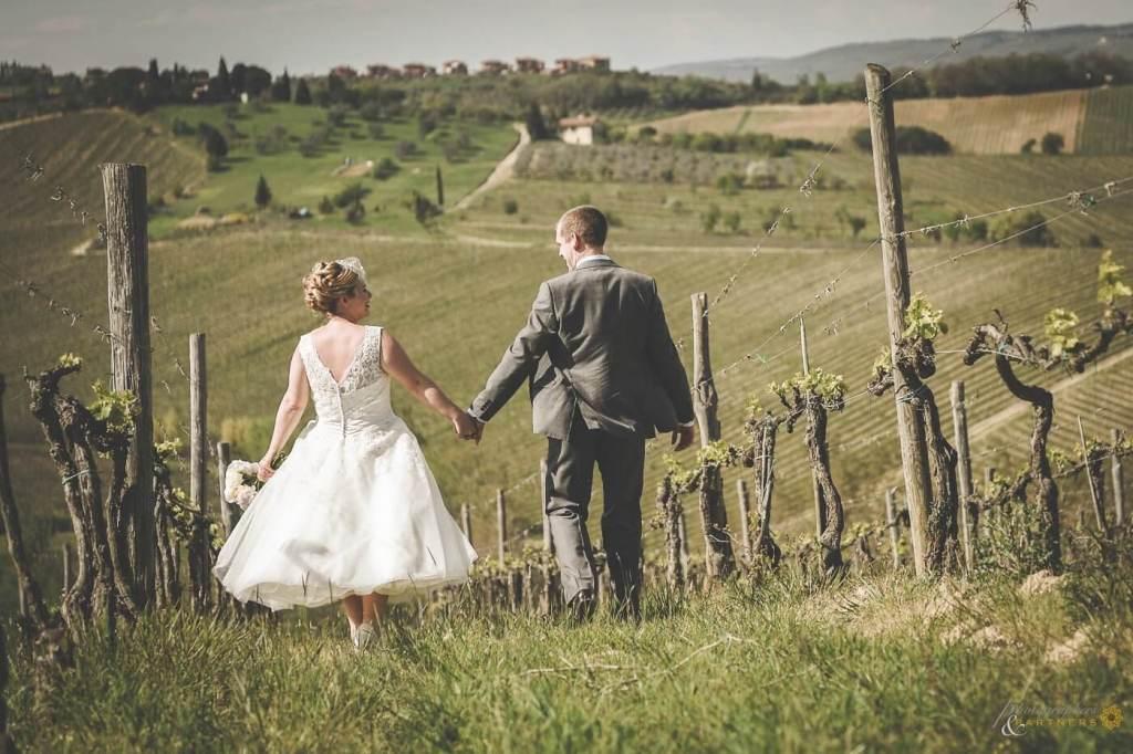 Emma & Alex walk through the vineyards in the Chianti hills