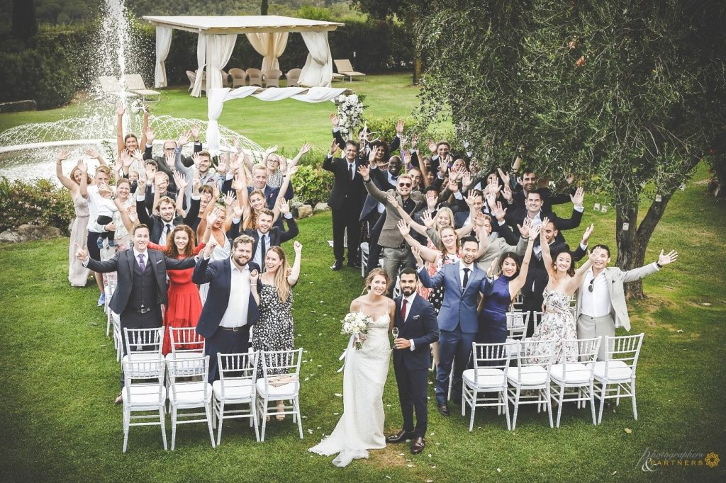 The newlyweds make a photo with their guests after the ceremony