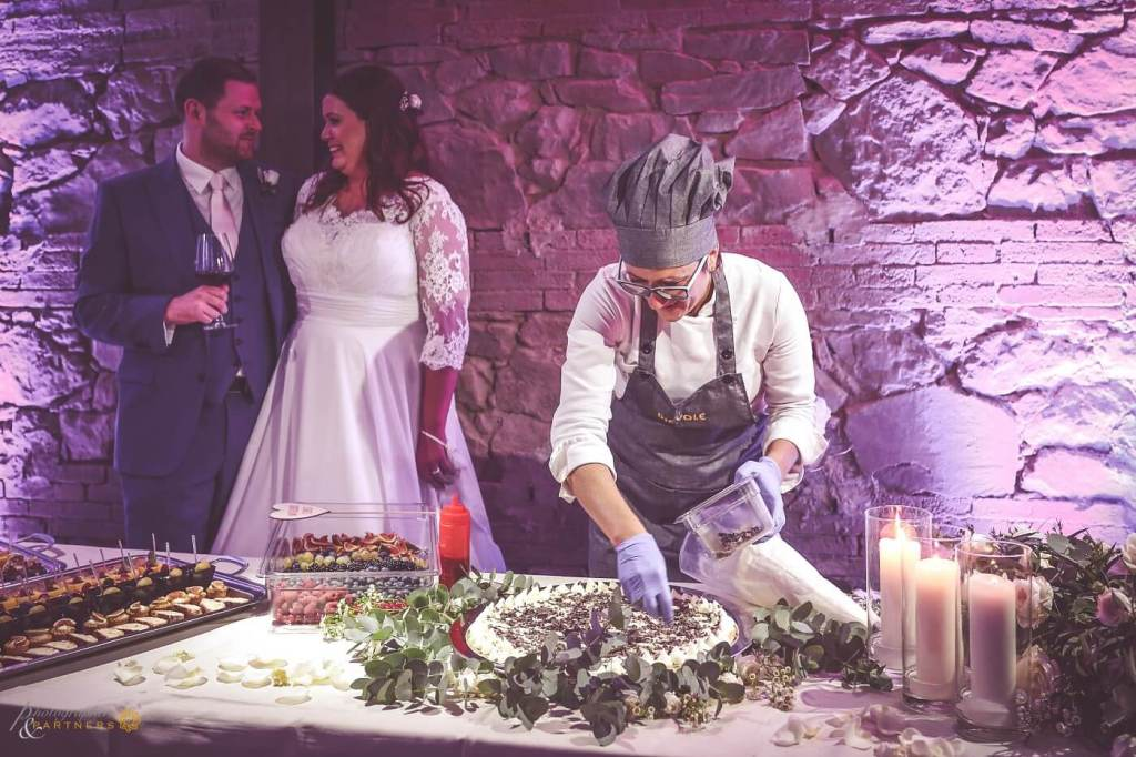 A pastry chef prepares the wedding cake