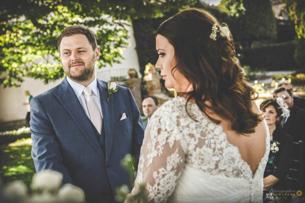 Bride and groom at wedding ceremony listen to registrar speech before exchanging rings