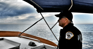 Officer Sundberg scans the water surface and horizon looking for a disabled small boat before a  storm blows in.