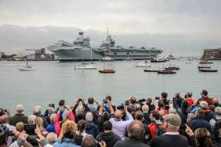 HMS Queen Elizabeth, the largest warship ever built for the Royal Navy arriving in Portsmouth Harbour for the first time. The aircraft carrier has no catapults or arrestor wires and is designed to operate vertical short take off and landing aircraft