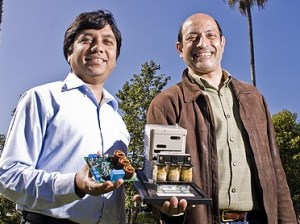 Primit Parikh, left, and Umesh Mishra founded Transphorm, which aims to reduce wasted heat energy. Parikh holds one of Transphorm's systems; Mishra displays an older technology. (Stephen Nellis / Business Times file photo)