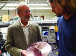 John Bowers and researcher Tin Komljenovic with a wafer of integrated photonic circuitry to be developed by AIM.