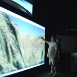 Andrew Lucas, an IT tech specialist at Ventura College, wears 3D goggles as he tries out a giant touch screen computer.