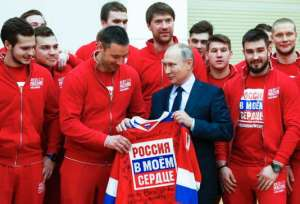 "Russian President Vladimir Putin, centre right, holds a jersey while posing for a photo with Russian national ice hockey team during a meeting with the Russian athletes who will take part in the upcoming 2018 Pyeongchang Winter Olympic Games in South Korea, at the Novo-Ogaryovo residence outside in Moscow, Russia, Wednesday, Jan. 31, 2018. As punishment for what it deemed a doping scheme during the 2014 Sochi Olympics, the International Olympic Committee has invited 169 Russians to compete under a neutral flag using the name ""Olympic Athletes from Russia."" (Grigory Dukor/Pool Photo via AP)"