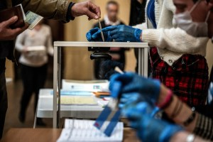 A voter casts their ballot in front of an official wearing plastic gloves in a polling station of Lyon on March 15, 2020 during the first round of the mayoral elections. - Officials have been told to disinfect voting booths and ballot boxes throughout the day, and sinks and hand gels will be made available. People will be urged to get in and out quickly to avoid lines, and floor markings will be laid out to ensure they stay one metre (3.3 feet) from one another. Authorities have already eased proxy voting rules for people at risk or infected with coronavirus and ordered to confine themselves to their homes, as well as for people in retirement homes. People can also come with their own pens for marking ballots. (Photo by JEFF PACHOUD / AFP)