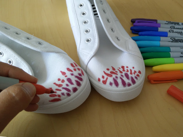 Colouring in the canvas shoes with sharpies