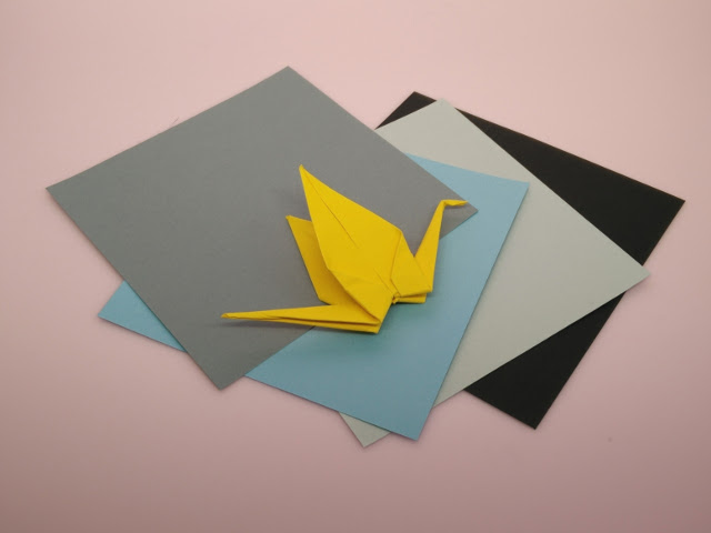 Squares of coloured paper ready to make the paper cranes