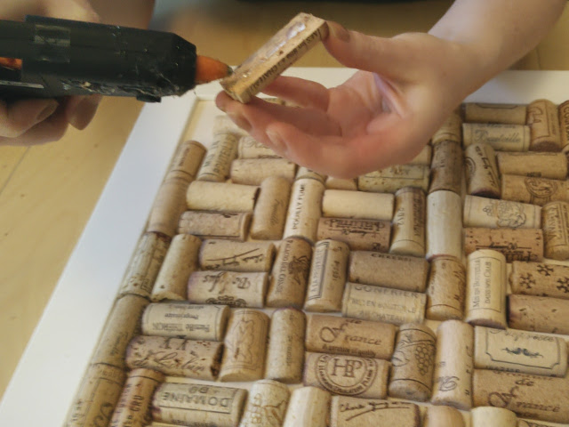 Gluing the corks to the frame with a glue gun