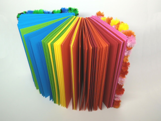 A rainbow notebook with woven pipe cleaners