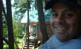 Chris on the porch of a cabin at Gorman Chairback Lodge