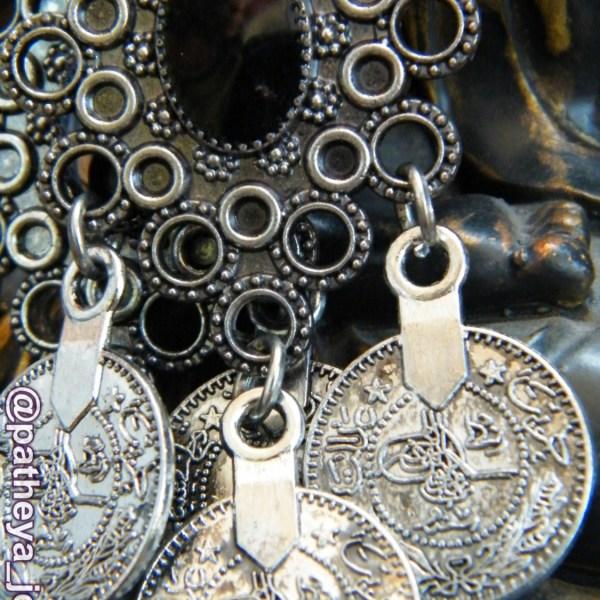 Detail of drop coin earrings