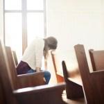 woman alone in church pew