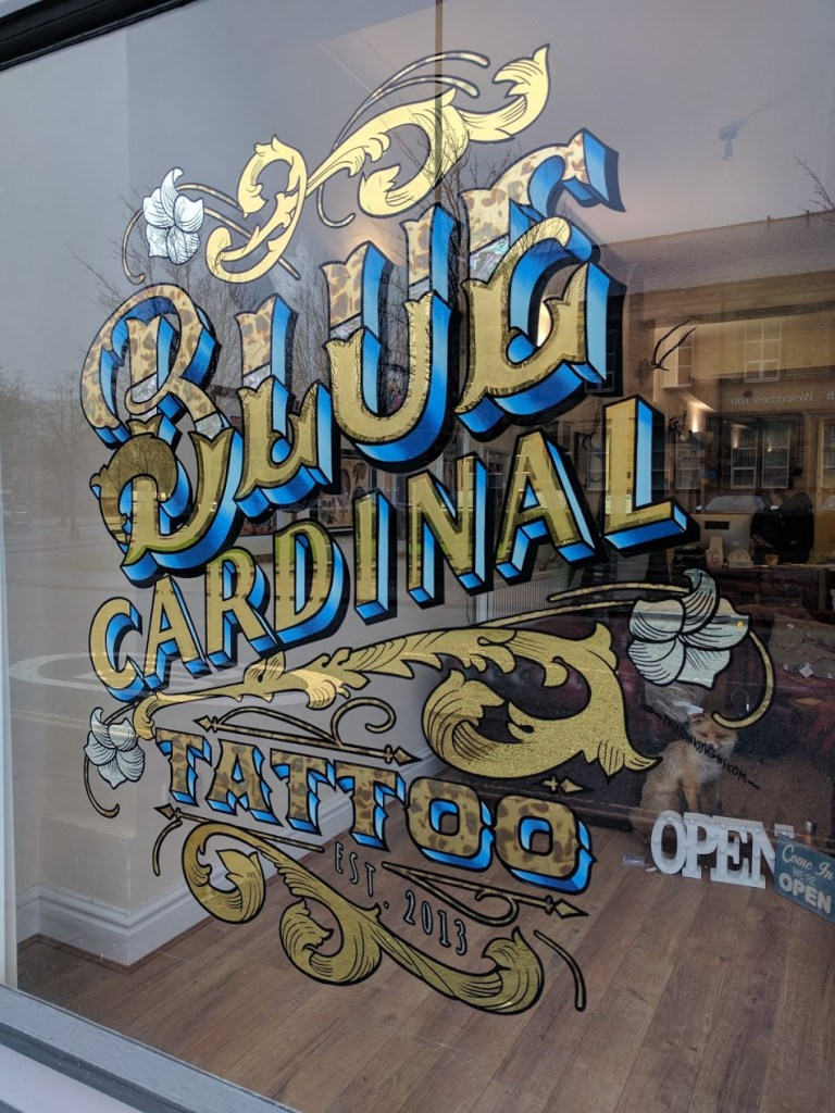 Blue Cardinal Tattoo gold leaf sign