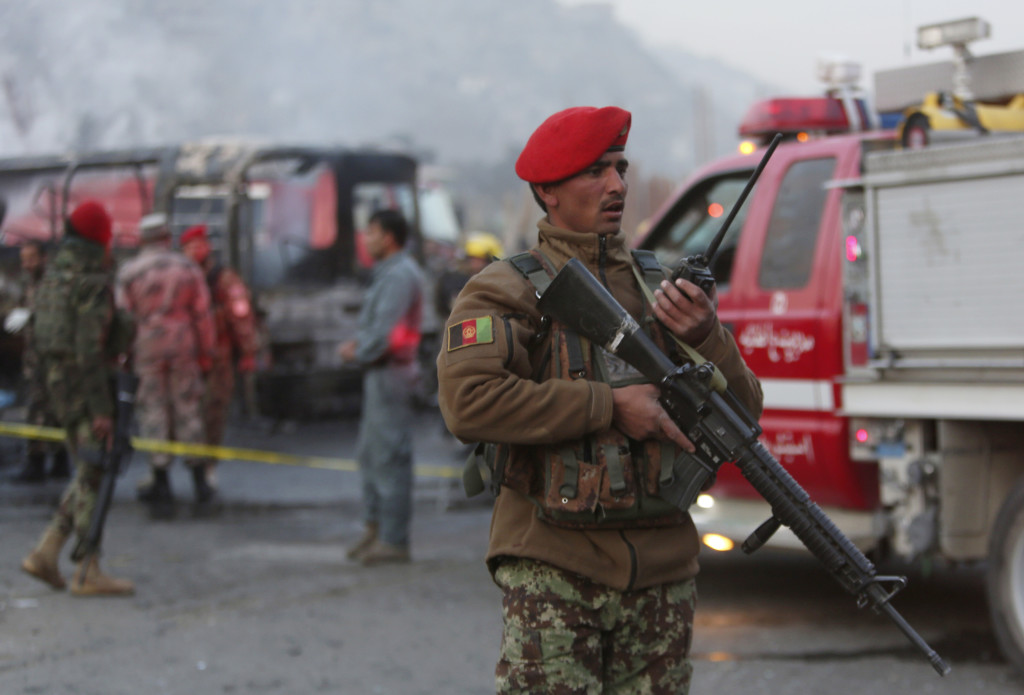 An Afghan soldier stands guard standing by a damaged bus at the site of a suicide attack by the Taliban in Kabul, Afghanistan, Saturday, Dec. 13, 2014 .