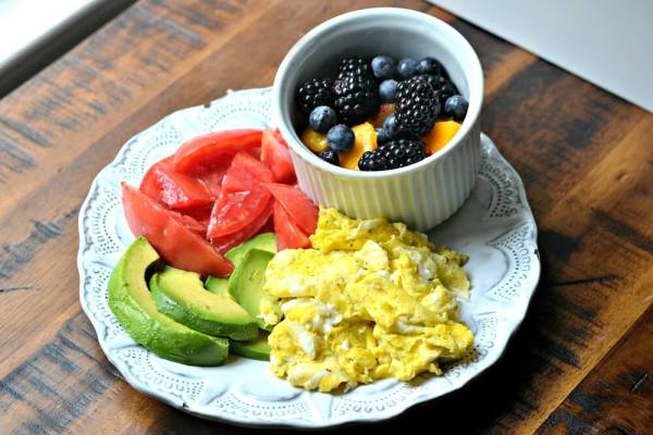 Eggs, homegrown tomatoes, sliced avocado and blackberries, peaches and blueberries
