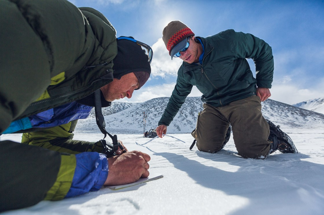 Gregg Treinish extends a ruler to measure the stride of a large felid track while Jason Wilmot records measurements. The pair concluded that this was probably a Snow Lepoard track.