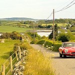 Strangford Lough at Killinchy, Co. Down, Northern Ireland. E-type Jaguar motorcar driving on country lane.