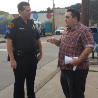 Eli Kuti (r) talks with a police officer from Pittsburgh ahead of an LGBTQ Rally