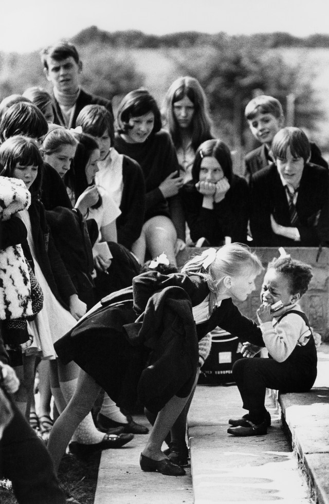 Vintage 1969 black and white print scan secondary school pupils crowd round a little black girl who has fallen and is crying at Maltby Grammar School sports day. Note the black child was one of twins from the only coloured family in this Yorkshire mining town and at this time there was no discrimination just a lot of attention.