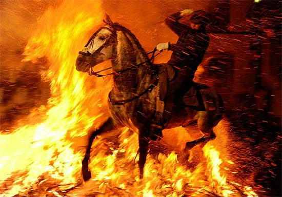 A man rides a horse through a bonfire on January 16, 2012 in the small village of San Bartolome de Pinares, Spain - Jasper Juinen/Getty Images