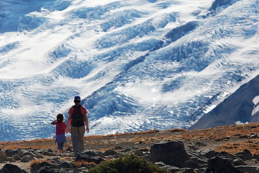 Mother and daughter hikers hiking on First Burroughs Mountain with Emmons Glacier ice in background, Mount Rainier National Park, Washington