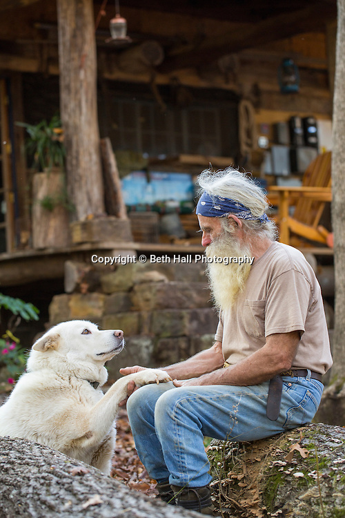 Robert Runyan sits with his dog Athena outside of his home in Sugar Tree Hollow in Winslow, Arkansas, for Out Here Magazine. Photo by Beth Hall (Beth Hall)