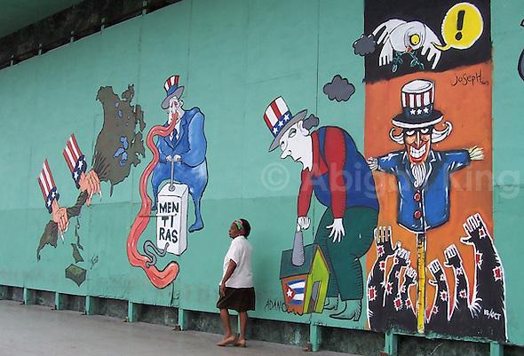 "Woman walks past street art in Cuba. Message reads ""Lies"""