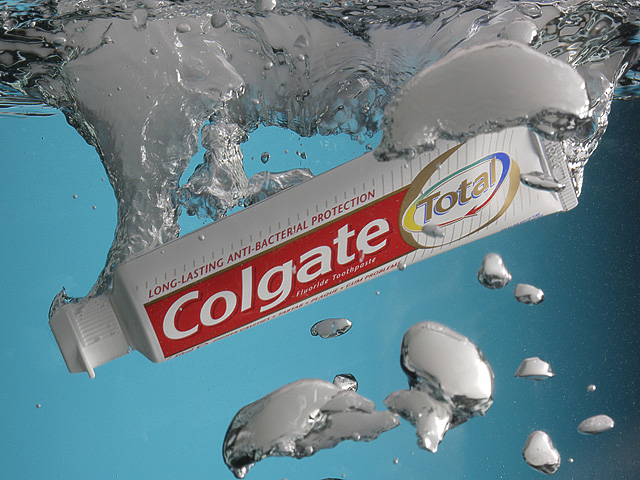 Colgate Total protection toothpaste dropped into water.