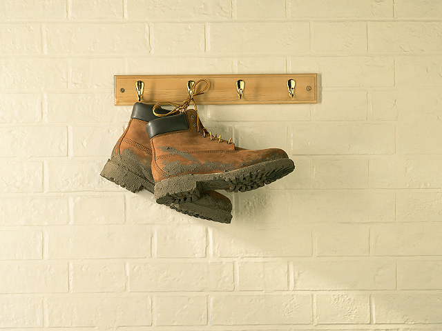 muddy walking or hiking boots, hanging against a brick wall.