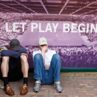 Two fans sit against a poster as they wait for play to begin after rain delayed play at the Wimbledon tennis championships in London June 27, 2008.