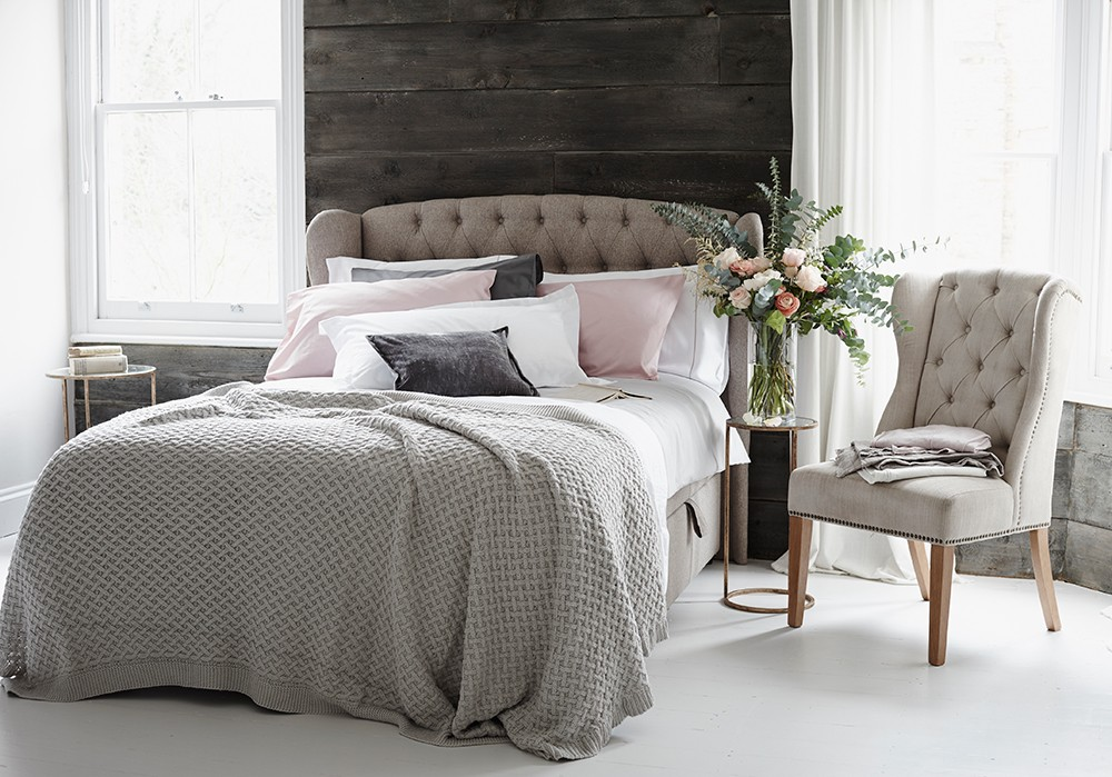 Faded linen bedding on a button-back headboard against a wood-clad wall. Next homeware styled by Pippa Jameson and photographed by Jo Henderson.