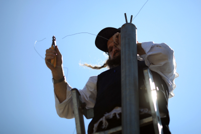 "An Ultra Orthodox Jewish man stands on a  ladder and hangs ""Eruv"" (Eiruv or Erub) wire, near the Gilo neighborhood in south Jerusalem, on Friday, Aug 14, 2009. A community Eruv refers to the legal aggregation or ""mixture"" under Jewish religious property law of separate parcels of property meeting certain requirements into a single parcel held in common by all the holders of the original parcels, which enables Jews who observe the traditional rules concerning Shabbat to carry children and belongings anywhere within the jointly held property without transgressing the prohibition against carrying a burden across a property line on the Jewish sabbath. Photo by Nati Shohat / FLASH90. *** Local Caption *** òéøåá çåè òîåã çøãéí çøãé éøåùìéí"