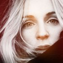 A close cropped black and white image of singer Agnes Obel which has then been coloured with maroon and orange hues.