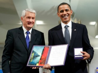 Nobel Peace Prize laureate U.S. President Obama poses with his medal and certificate as Norwegian Nobel Committee Chairman Jagland stands with him in Oslo Hall