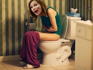 Woman in pain on toilet in bathroom