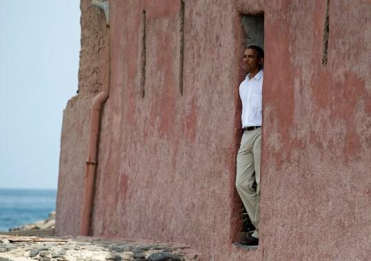 """Una de las primeras paradas de Barack Obama al llegar a Senegal fue a la isla Gorée, uno de los centros de tráfico de esclavos con destino a América en el siglo XVIII. Esta foto del primer presidente negro estadounidense en la """"puerta del no retorno"""" es de lo más emotiva."""