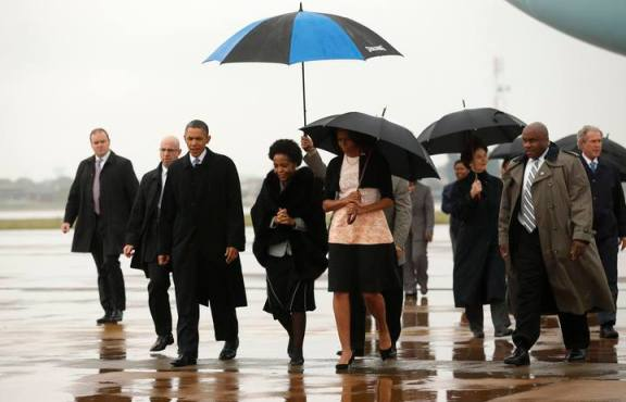 U.S. President Barack Obama and first lady Michelle Obama are escorted upon their arrival on Air Force One to attend a memorial service for Nelson Mandela in Johannesburg