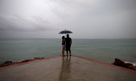 A couple looks out to sea as rainfall increases with the approach of Hurricane Patricia in Puerto Vallarta, Mexico, Friday, Oct. 23, 2015. Hurricane Patricia barreled toward southwestern Mexico Friday as a monster Category 5 storm, the strongest ever in the Western Hemisphere. (AP Photo/Rebecca Blackwell)
